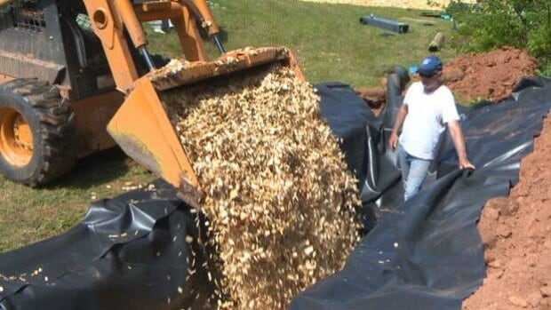 Wood chips are dumped into a trench to act as a nitrates filter protecting streams from nitrates.