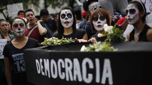 Protesters against Mexico's Institutional Revolutionary Party, or PRI, from the opposition movement Yosoy132 (I am 132) take part in a mock funeral for democracy during a march in Mexico City on Saturday.