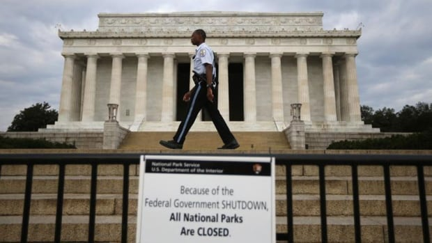 A U.S. National Parks policeman walks past a sign after the Lincoln Memorial was sealed off from visitors in Washington on Oct. 1, 2013.