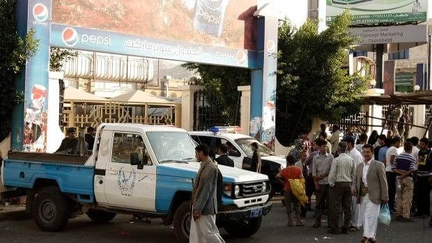 Policemen and civilians gather outside a supermarket after a shooting in Sanaa, Yemen. A Yemeni security official says unknown gunmen killed a German embassy guard in an attack on a diplomatic vehicle outside a supermarket in the country's capital.