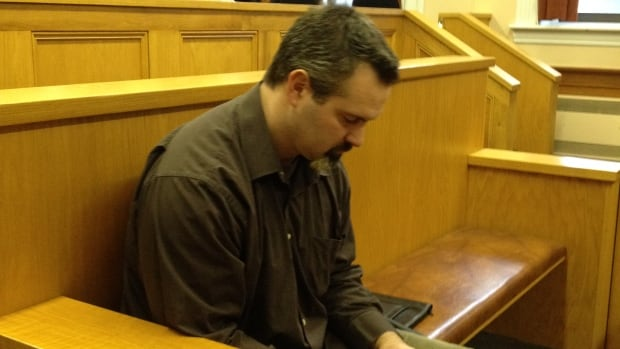 David Folker, 42, used his cell phone while he waited in court on Monday.