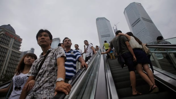 People takes the escalators in Shanghai, China's financial hub. The World Bank predicts the Chinese economy will grow at 7.5 per cent, down from the 8.3 per cent it forecast earlier this year.
