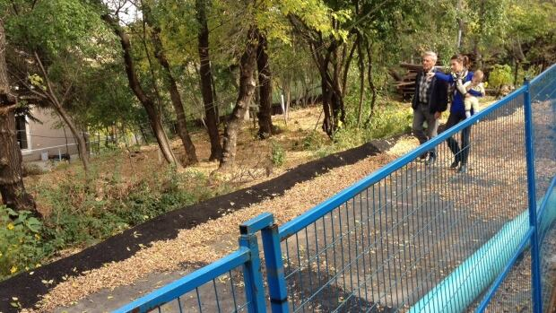 Joni Rynsburger-Rathwell walks the ridgeline that is threatening to slide into her Sask Crescent East home.