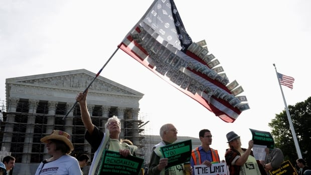 A demonstrator holds a flag covered in money and corporate logos during a rally outside the U.S. Supreme Court in Washington on Tuesday, as the court heard a campaign-finance case that could let rich donors pour considerably more money into U.S. federal politics.