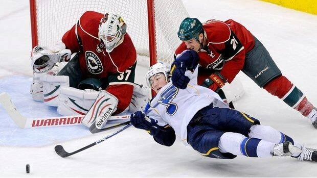 St. Louis Blues' T.J. Oshie reaches for the puck as he falls while giving chase around the net against Minnesota Wild's Kyle Brodziak (No. 21) and goalie Josh Harding Saturday night. The Wild won 2-1.