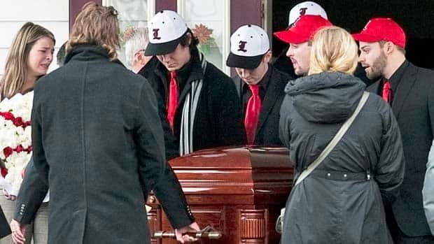 Members of the Lethbridge Bulls baseball team carry the casket of teammate Mitch MacLean at his funeral at Winsloe United Church in Winsloe, P.E.I., on Thursday. MacLean, fellow player Tanner Craswell and Tabitha Stepple of Lethbridge, Alta., were killed in a roadside shooting in Alberta last week.