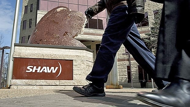 People walk past the headquarters of Shaw Communications in Calgary, Alta. The company has cancelled its wireless network plans.
