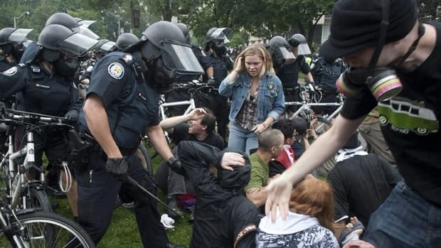 Police clear protesters outside the provincial government buildings in Toronto during last June's G20 summit. A new report looks at protests and security measures at the summit.