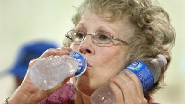 A woman uses one bottle of water to cool her neck and drank from another in the U.S., where temperatures have also been high in July.