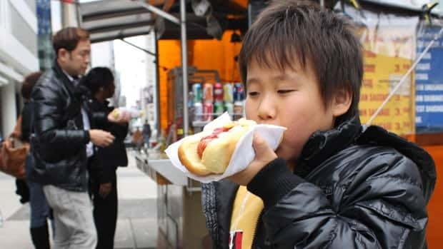 Dan Karasawa, 8, takes a bite out of his first Canadian hot dog as his father grabs another one for the elder son.