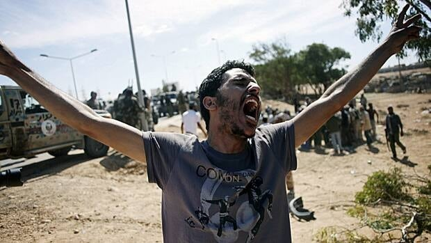 A revolutionary fighter celebrates in the captured town of Sirte, Libya.