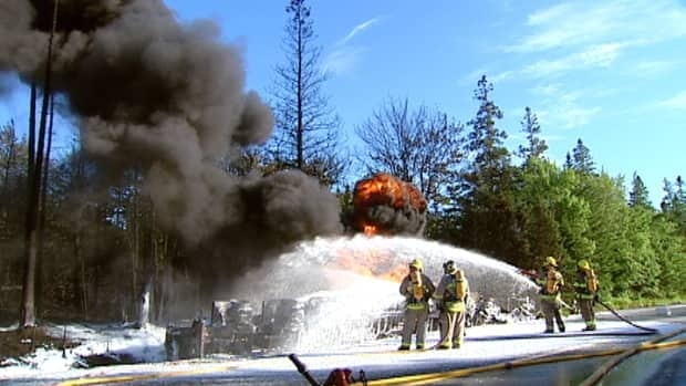 Firefighters douse flames after a tractor trailer carrying fuel collided with a car on Highway 103.