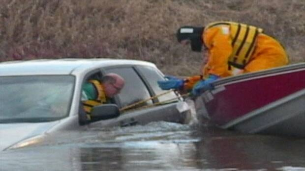 A man was trapped in his vehicle as water from a swollen Swift Current Creek rushed by. He was rescued moments before the van was swept away.
