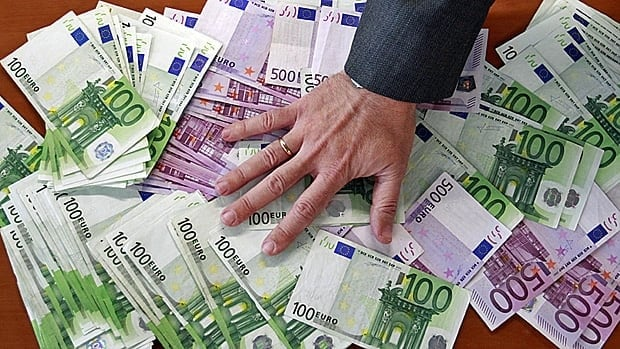 A bank employee spreads out euro notes on a table at a bank branch in Madrid. The rate Spain pays to borrow money has gone above the unsustainable 7 per cent level.
