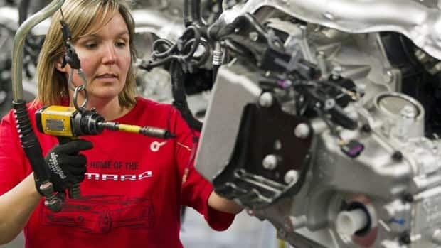 Engine specialist Jennifer Souch assembles a Camaro motor at the GM factory in Oshawa in June. GM says it will spend $117 million at the facility to assemble the Cadillac XTS.