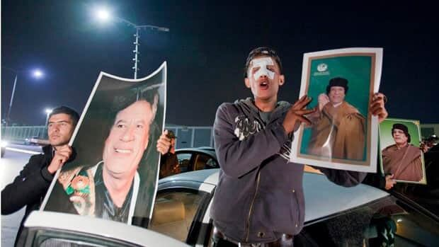 Supporters of Moammar Gadhafi chant slogans following a NATO airstrike in Tripoli early Saturday.