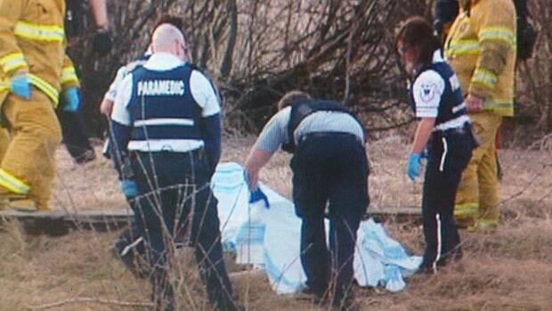 Rescue workers recover the body of a male from the swollen waters of Wascana Creek in Regina.