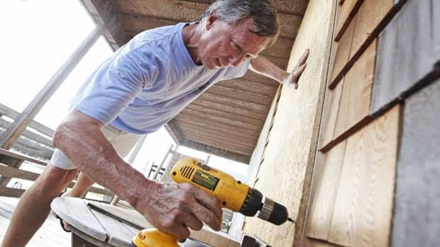 Pike Harrington of Nags Head, N.C., boards up his beach house on Aug. 25, 2011, in preparation for Hurricane Irene.