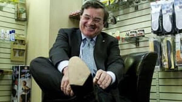 Finance Minister Jim Flaherty puts on his newly resoled shoes during a pre-budget photo op at an Ottawa shoe repair store on Monday, March 21, 2011.