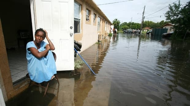 A woman sits outside her home along a flooded streetin Ft. Lauderdale, Fla., in October. Absolute economic losses due to extreme weather are higher in developed countries, but deaths and economic losses as a proportion of the GDP are far higher in developing nations.
