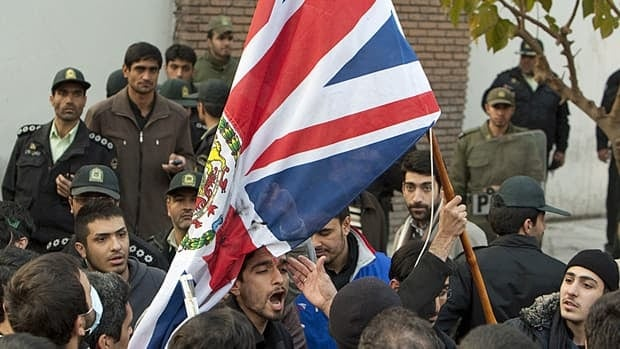Protestors remove the flag of the British Embassy in Tehran on Tuesday.