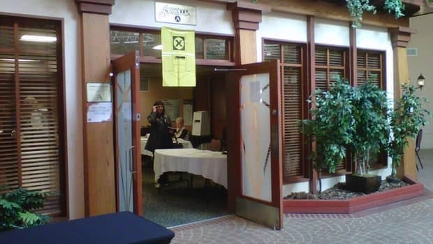 Elections Canada staff work at a Winnipeg polling station on Monday. There are at least two judicial recounts expected after Monday's election.
