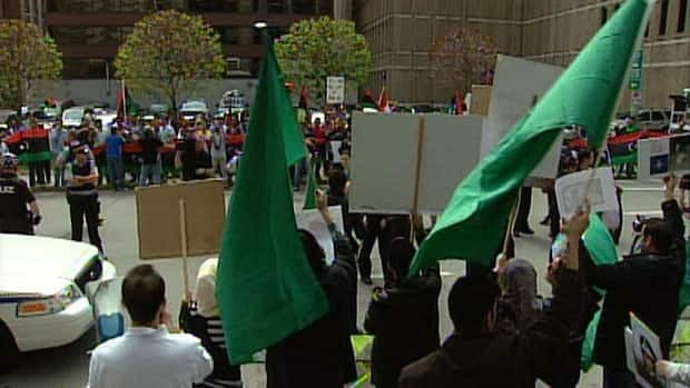 Demonstrators supporting Libyan leader Moammar Gadhafi, foreground, square off across the street from people who oppose him outside the Libyan Embassy in Ottawa on May 13. Canada is expelling five diplomats from the embassy.
