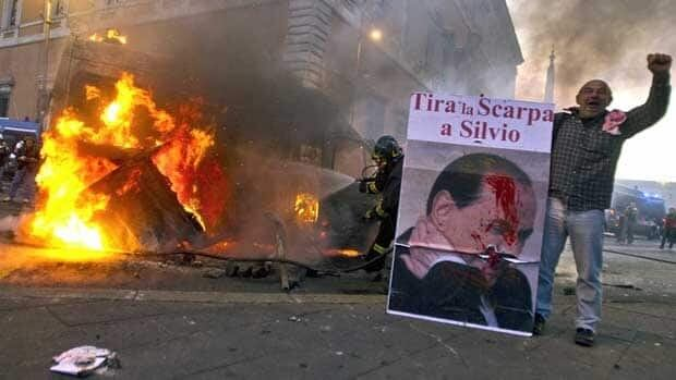 """A man standing next to a burning Carabinieri vehicle in Rome shows a placard depicting Italian Premier Silvio Berlusconi which reads """"Throw the shoe at Silvio"""" in Italian. Protesters there hurled rocks and incendiary devices at police and banks."""