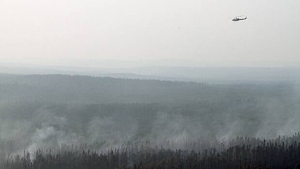 A helicopter flies in smokey conditions near Kenora, Ont.