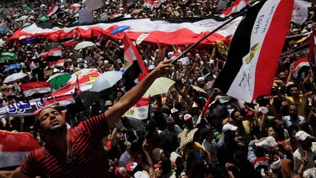 A protester waves an Egyptian flag after Friday prayers in Tahrir Square where many have set up protest tent camps in the main city square in Cairo, Egypt.