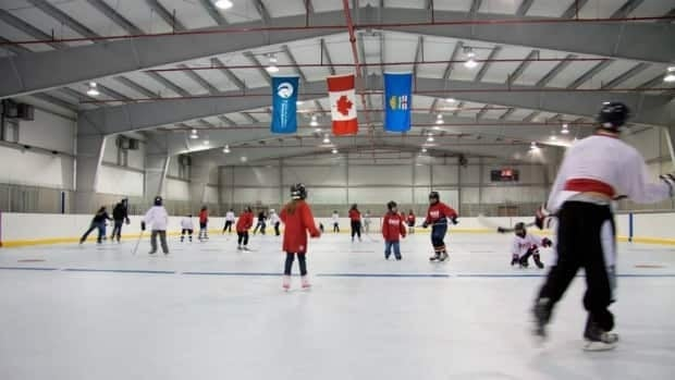 Skaters in Fort Chipewyan try out North America's first NHL-sized synthetic ice rink on its opening day last December. Cracks and bumps appeared in the surface only a few months later, prompting officials to tear up the $550,000 surface.