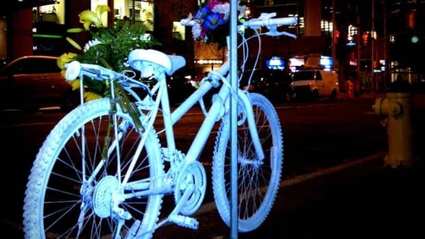 A ghost bike memorial sits, along with some flowers, near where a woman in her 30s died after hitting a car door opened from a parked car in downtown Ottawa.