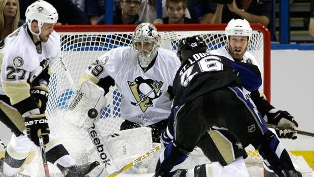 Pittsburgh Penguins goalie Marc-Andre Fleury (29) makes a save on a shot by Tampa Bay Lightning right wing Martin St. Louis (26) as Penguins right winger Craig Adams (27) moves in during the first period in Game 6 on Monday in Tampa, Fla.
