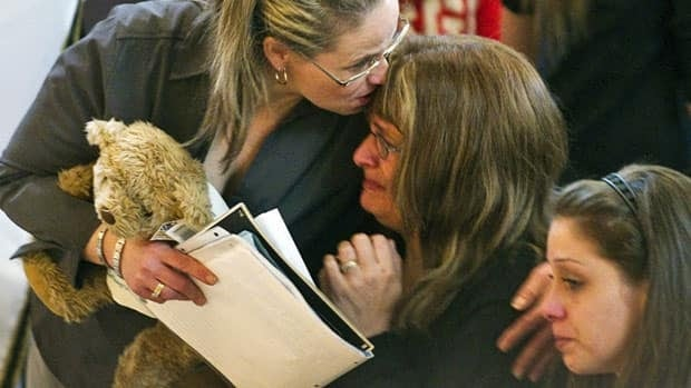 Jolène Riendeau's mother, Dolores Soucy, centre, is comforted by her sister, Johanne, during funeral services on Friday in Montreal.