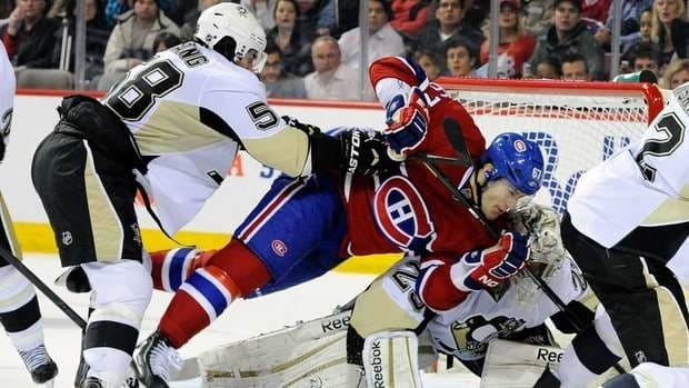 Kris Letang, left, of the Pittsburgh Penguins pushes Max Pacioretty, right, of the Montreal Canadiens into teammate Marc-Andre Fleury during their game Saturday night. Paciorietty has been suspended for three games because of an illegal hit he delivered to Letang later in the game.