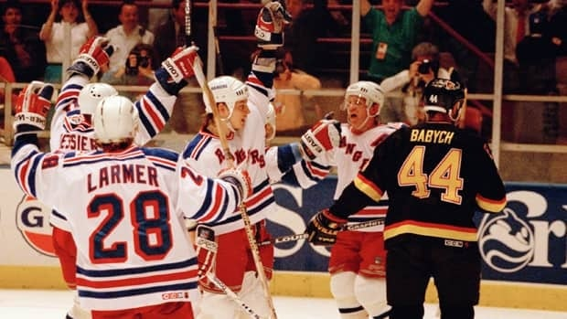 Canucks defenceman Dave Babych (44) skates away as members of the Rangers celebrate a goal in Game 7 on June 14, 1994.