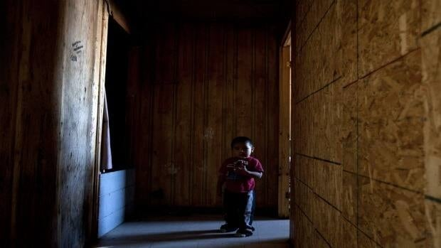 A young boy stands in the hallway of a house condemned due to structural and mould problems. He shares the home with three other people in Attawapiskat.