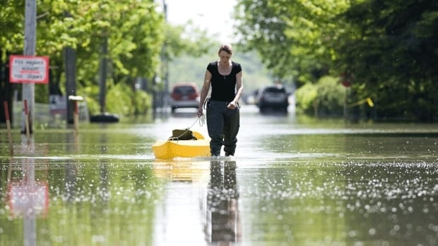 Céline Bourassa drags a kayak along a street immersed in flood waters in the town of St-Blaise-sur-Richelieu, Que., on May 30, 2011. Parts of Quebec on Ontario had their wettest spring on record this year.