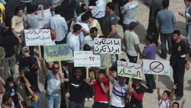 Protesters gather in a square in the southern Syrian city of Deraa on Thursday in an image sent to the Reuters wire service. Banners read 'To be or not to be,' centre, and 'We want freedom and not slavery amendment,' left.