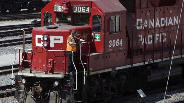 A Canadian Pacific Railway employee walks along the side of a locomotive in a marshalling yard in Calgary.