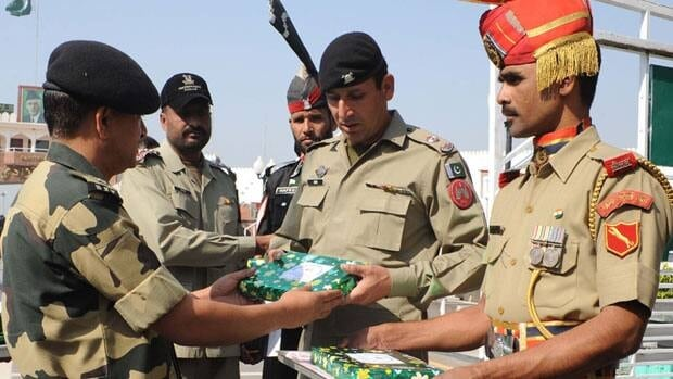 Indian border police Cmdr. Susheel Negi, left, hands a basket of sweets to Pakistani Rangers Supt. Major Asim, centre, at the India-Pakistan border on Oct. 26, the day of the Hindu and Jain festival Diwali. Trade relations between the countries are set to improve.