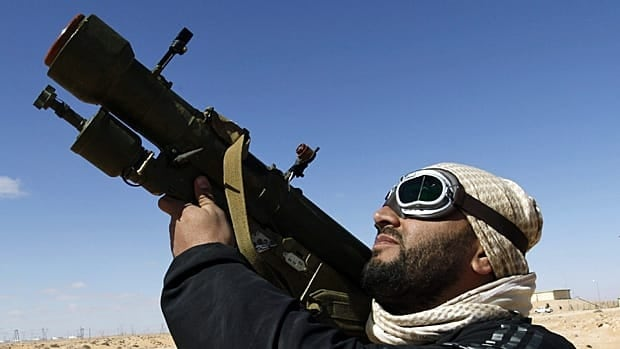 A Libyan rebel fighter holds an anti-aircraft missile launcher on Sunday as he looks to the sky in the oil town of Ras Lanouf in eastern Libya. (Hussein Malla/Associated Press)