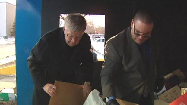 Gary Dickson, left, and an assistant look inside a paper-recycling bin where they discovered thousands of intact medical files.