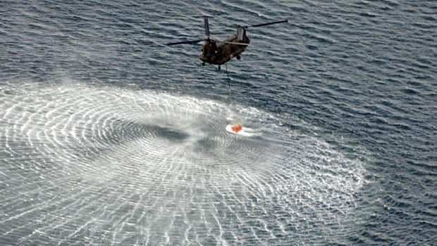 A Japanese helicopter collects water from the ocean to drop on the reactors at the Fukushima Daiichi nuclear plant on Thursday.
