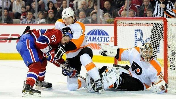 Philadelphia Flyers forward Sean Couturier, centre, clears Montreal's Mathieu Darche, left, from in front of goaltender Sergei Bobrovsky on Thursday night.