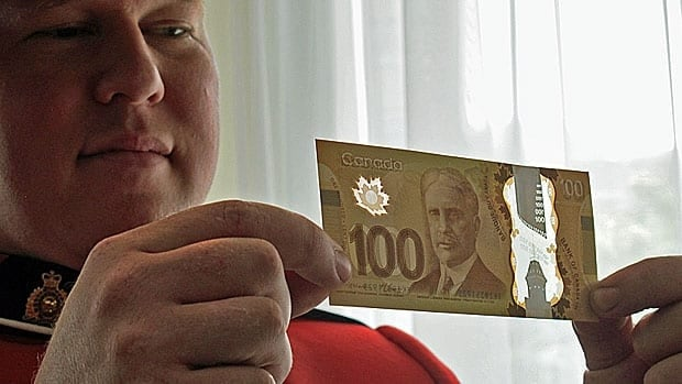 An RCMP officer displays the new bills, which are harder to counterfeit.