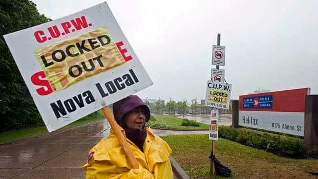 A locked-out Canada Post employee pickets outside the main postal facility in Halifax on Saturday.