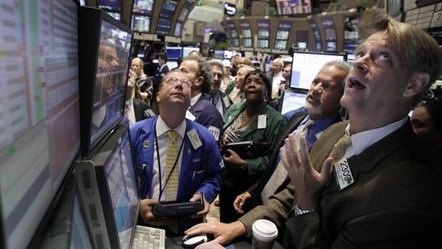 Traders crowd the post of specialist Patrick Murphy, right, on the floor of the New York Stock Exchange on Thursday, as the Dow Jones industrial average surged more than four per cent.
