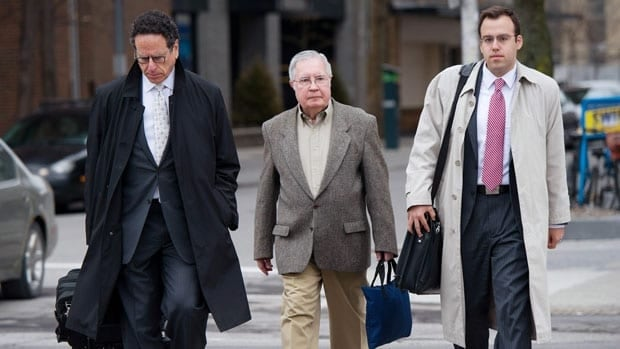 Bishop Raymond Lahey (centre) arrives at an Ottawa court with his lawyers on Wednesday for his child pornography trial.