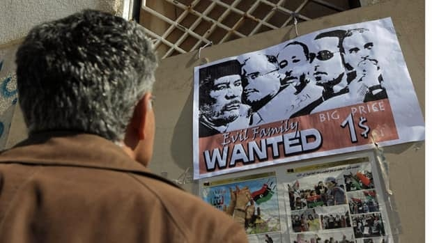 "A man inspects a poster opposing Libyan leader Moammar Gadhafi during protests in Benghazi, Libya. The Arab League has asked the UN Security Council to impose a no-fly zone over the North African nation, declaring Gadhafi's government has ""lost its sovereignty."""